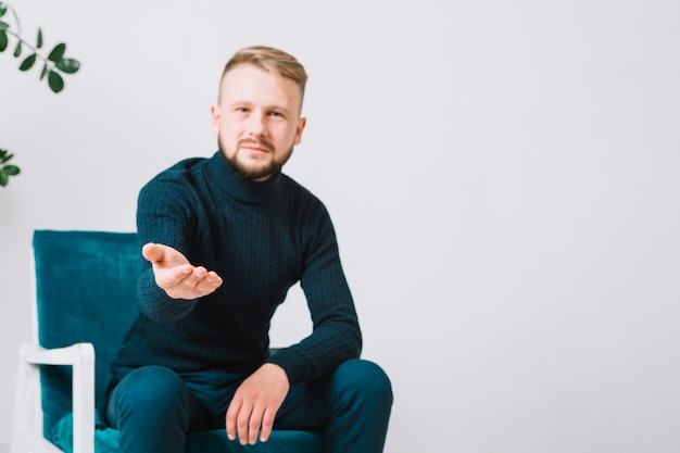 Mannelijke psycholoog die helpende hand bij camera voor handdruk tegen witte muur uitbreiden