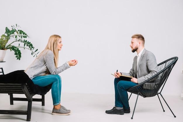 Mannelijke psycholoog die voor vrouwelijke patiënt zit die aan haar probleem luistert