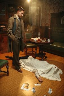 Mannelijke rechercheur in jas kijkt naar slachtoffer onder de cape op de plaats delict