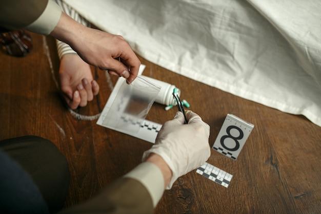 Mannelijke rechercheur met pincet verzamelt bewijsmateriaal op de plaats delict