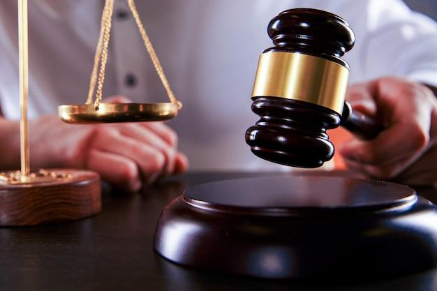 Mannelijke rechter sloeg houten hamer op het bureau. advocaat concept.