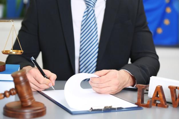 Mannelijke rechter werkt met document- en wetaccessoires op tafel