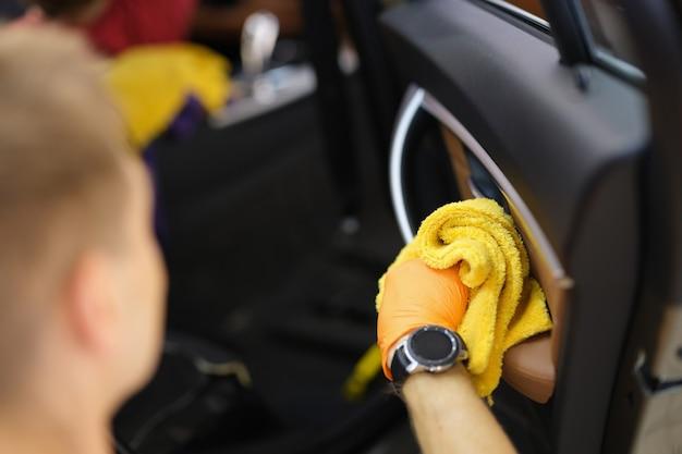 Mannelijke reiniger die stof in het interieur van de auto afveegt met een close-up van een microvezeldoek