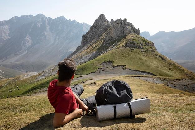 Mannelijke reiziger die op bergen wandelt terwijl hij zijn benodigdheden in een rugzak heeft