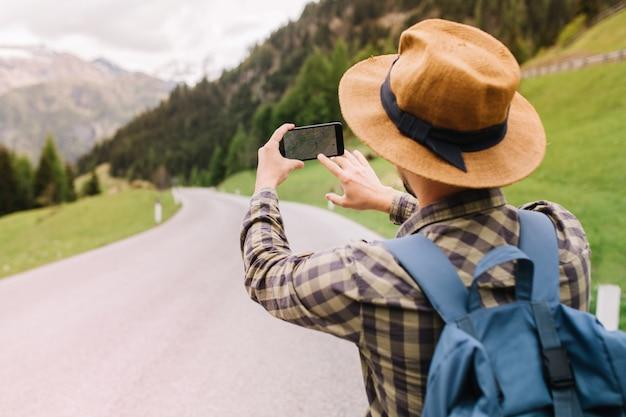 Mannelijke reiziger in bruine hoed die de juiste weg zoekt door online kaart te gebruiken die zich op mooie berg bevindt