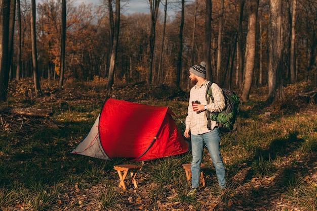 Mannelijke reiziger met drankje mee en rugzak op camping