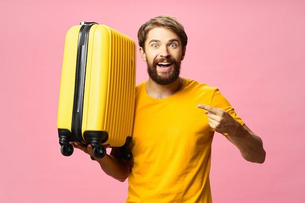 Mannelijke reiziger met een koffer in zijn handen poseren
