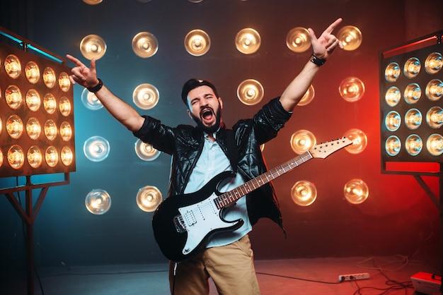 Mannelijke rockster met elektrische gitaar handen omhoog op het podium met de decoraties van lichten.