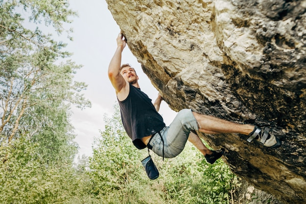 Mannelijke rotsklimmer die op de klip hangt