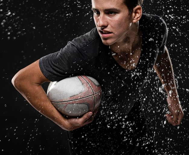 Mannelijke rugbyspeler met bal en waterspatten