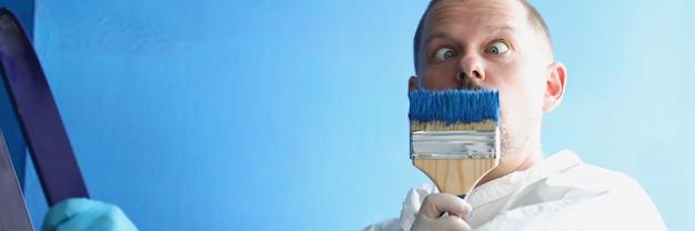 Mannelijke schilder houdt penseel bij zijn gezicht
