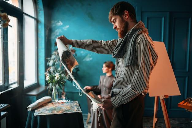 Mannelijke schilder kijken naar canvas schilderij tegen vrouwelijke poseur in tekenstudio.