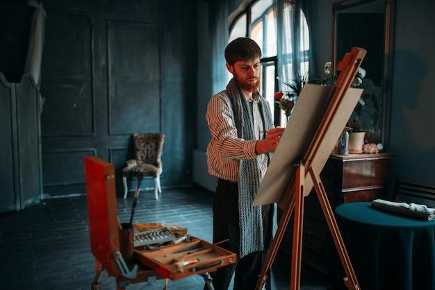 Mannelijke schilder met penseel in hand voor ezel.