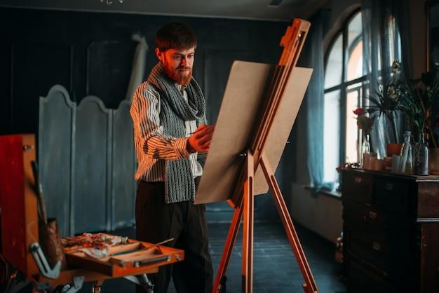 Mannelijke schilder met penseel voor ezel