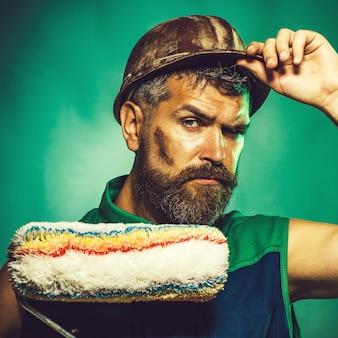 Mannelijke schilder met verfroller professionele schilder met verfroller in beschermende helm
