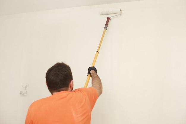 Mannelijke schilderij muur met verfroller. appartement schilderen, renoveren met witte kleur verf. kamerrenovatie in huis.