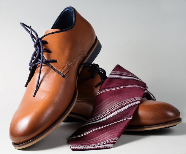 Mannelijke schoenen met stropdas over grijs