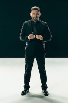Mannelijke schoonheid concept. portret van een modieuze jonge man met een stijlvol kapsel, gekleed in trendy pak poseren