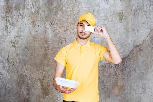 Mannelijke serviceagent in geel uniform met een witte afhaaldoos en zijn visitekaartje.
