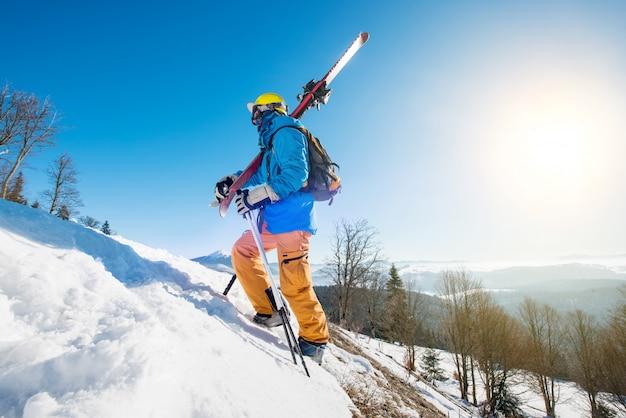 Mannelijke skiër die de helling in de bergen lopen die zijn skis dragen
