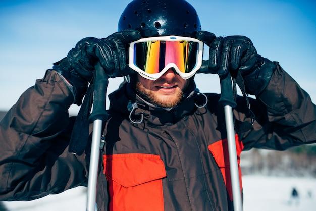 Mannelijke skiër in helm zet bril, vooraanzicht. actieve wintersport, extreme levensstijl. bergafwaards skiën