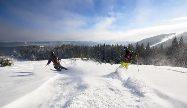 Mannelijke skiërs freeriden op een wijd open berghelling. extreem skiën tussen lage dennenbomen. panoramisch uitzicht op de bergen.