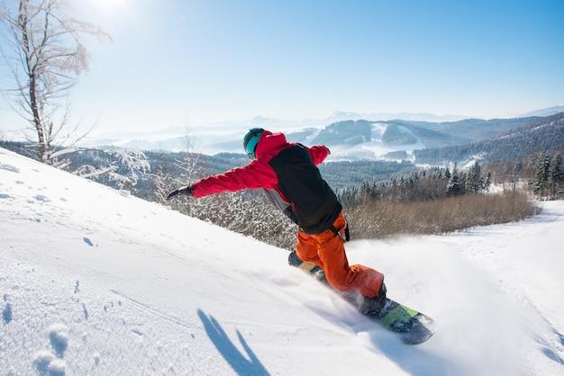 Mannelijke snowboarder die de helling berijdt