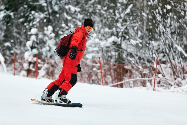 Mannelijke snowboarder in een rood pak rijdt op de besneeuwde heuvel met snowboard, skiën en snowboarden concept.
