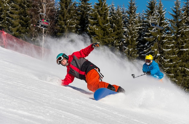 Mannelijke snowboarder skiën op de besneeuwde helling en professionele skiër cameraman schieten hem