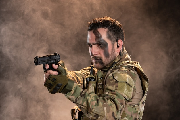 Mannelijke soldaat in camouflage die een pistool op de rokerige donkere muur richt