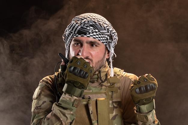 Mannelijke soldaat in camouflage die praat via radio op donkere muur
