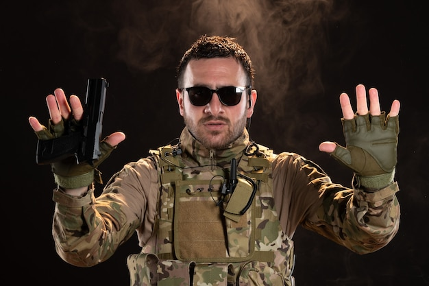 Mannelijke soldaat in camouflage die zich op donkere muur overgeeft