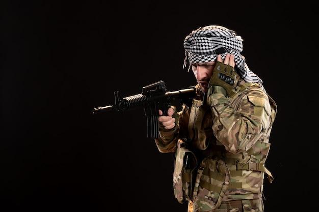 Mannelijke soldaat in camouflage gericht machinegeweer op zwarte muur