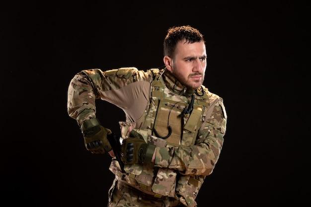 Mannelijke soldaat in camouflage gericht pistool op zwarte muur tank oorlog