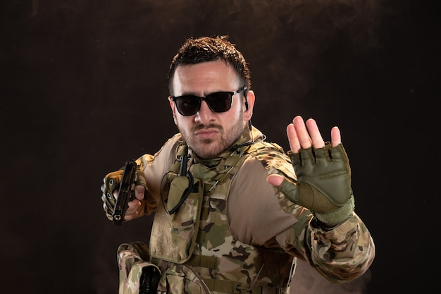Mannelijke soldaat in camouflage gevechten met pistool op donkere muur