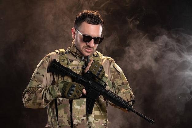 Mannelijke soldaat in camouflage met machinegeweer op donkere muur