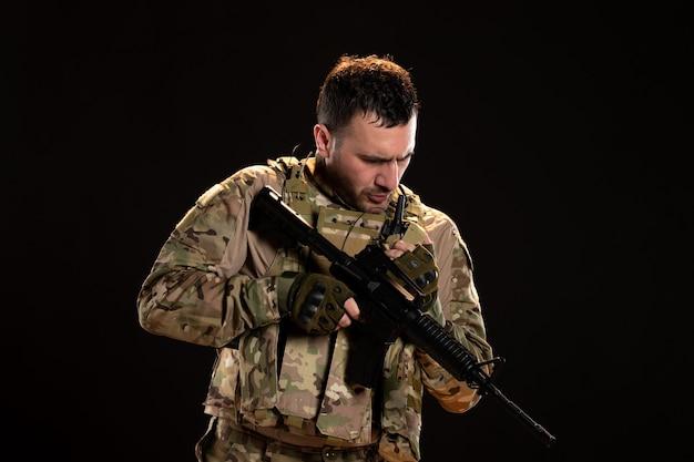 Mannelijke soldaat in camouflage met machinegeweer op zwarte muur
