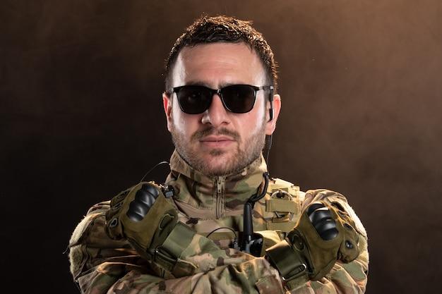Mannelijke soldaat in camouflage op de donkere muur