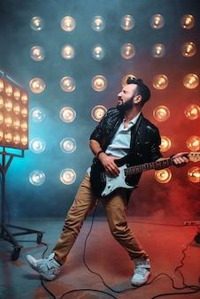 Mannelijke solo-gitarist met elektrische gitaar op het podium met de decoraties van lichten.