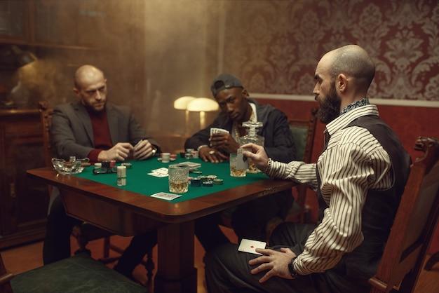 Mannelijke speler bedriegt in poker aan speeltafel, casino. verslaving, risico, gokhuis