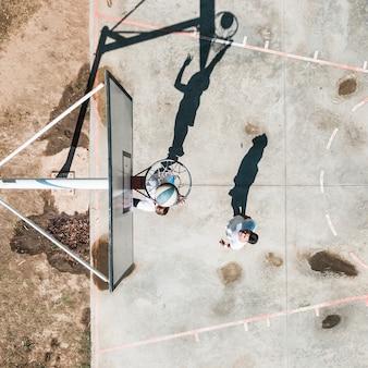 Mannelijke speler twee die met bal bij in openlucht hof uitoefenen