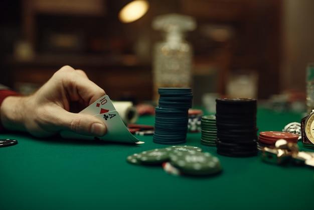 Mannelijke spelershanden met aas en tien kaarten, blackjack, casino, geluksverslaving.