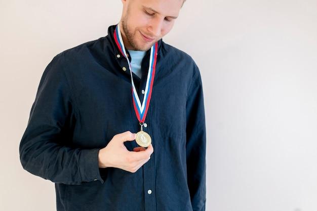 Mannelijke sportman met een gouden medaille op een borst, kampioensleider