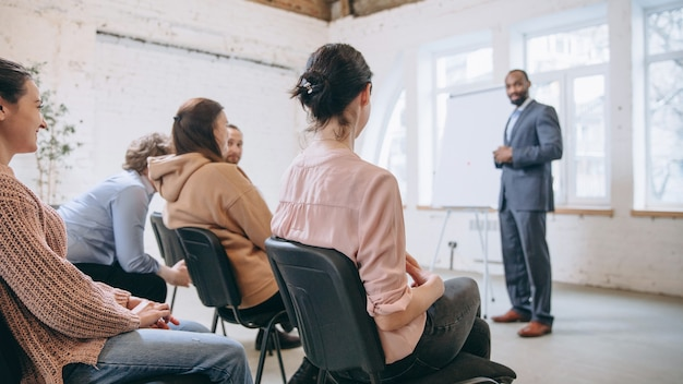 Mannelijke spreker geeft presentatie in hal op universitaire workshop. publiek of conferentiezaal