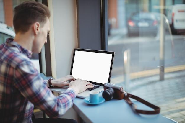 Mannelijke stafmedewerker met behulp van laptop aan balie