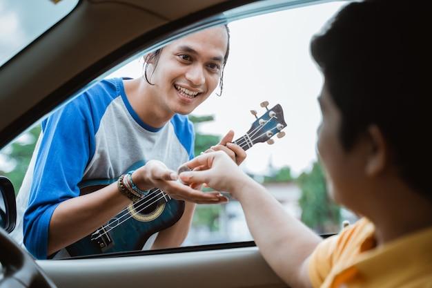 Mannelijke straatmuzikant die om geld bedelt