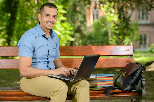 Mannelijke student die in openlucht gebruikend laptop in het park leert.