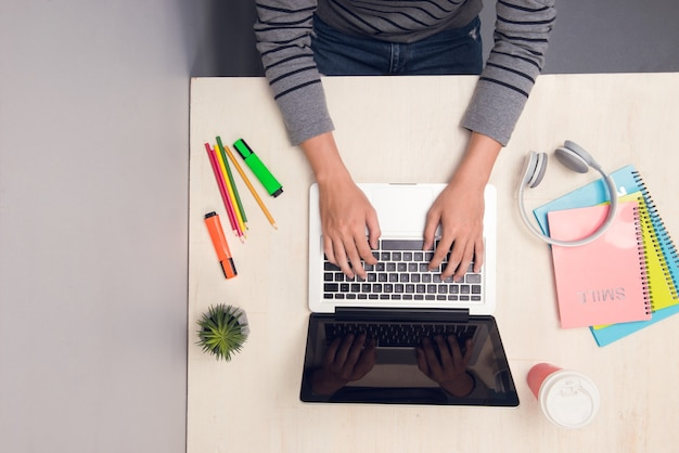 Mannelijke student die met laptop aan bureau werkt. bovenaanzicht