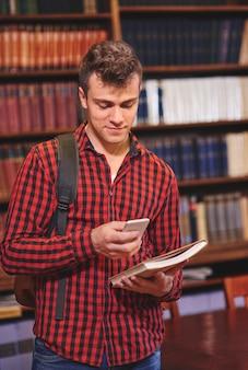 Mannelijke student die mobiele telefoon in bibliotheek gebruikt