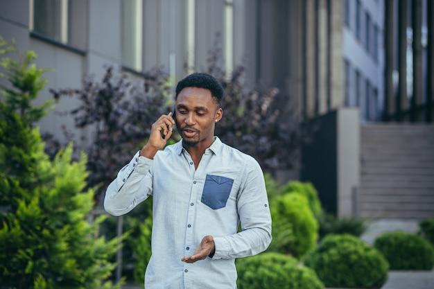 Mannelijke student die plezier heeft aan de telefoon in de buurt van een groot huis dat tijdens de lunch loopt